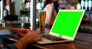 Cliente que usa un ordenador portátil con la pantalla verde en el contador de la barra almacen de video