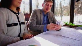 Cliente rico que paga o salário ao arquiteto fêmea pelo bom esboço no café vídeos de arquivo