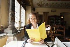 Cliente sonriente que lleva a cabo el menú en la tabla del restaurante Fotos de archivo libres de regalías