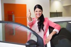 Cliente sonriente que se inclina en el coche mientras que da los pulgares para arriba Fotografía de archivo