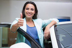 Cliente sorridente che si appoggia automobile mentre dando i pollici su Fotografie Stock Libere da Diritti