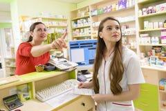 Cliente in una farmacia che indica un certo farmaco Immagine Stock Libera da Diritti