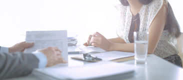 Cliente y agente que se sientan en el escritorio en una reunión o una colaboración acertada debajo de empresarios en oficina imagen de archivo libre de regalías