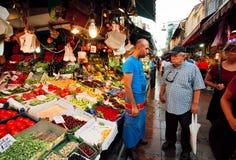 Cliente y comerciante serios del mercado de la comida Fotografía de archivo