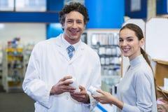 Cliente y farmacéutico sonrientes que sostienen la botella de la droga en hospital Fotos de archivo libres de regalías