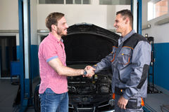 Cliente y mecánico sonrientes que sacuden las manos Imagenes de archivo