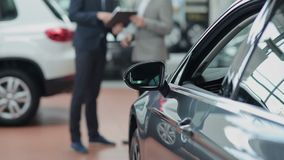 Cliente y vendedor borrosos detrás de un coche
