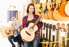 Clientes adolescentes que deciden sobre la guitarra acústica conveniente en guitarra Fotografía de archivo