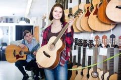 Clientes adolescentes que deciden sobre la guitarra acústica conveniente en guitarra Fotografía de archivo libre de regalías