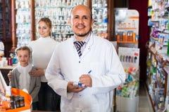Clientes de ajuda do farmacêutico Foto de Stock