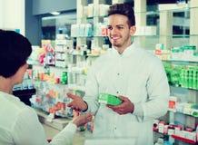 Clientes de ajuda do farmacêutico do homem na farmácia imagem de stock royalty free
