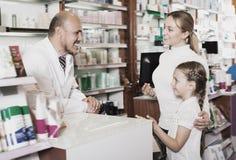 Clientes de ayuda de risa del farmacéutico de sexo masculino Imagen de archivo libre de regalías