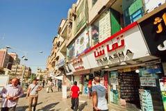 Clientes de precipitación que caminan más allá de tiendas electrónicas y de tiendas de la capital iraní Teherán Foto de archivo libre de regalías