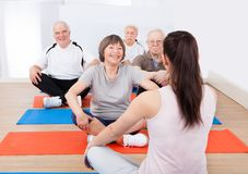 Clientes del entrenamiento del instructor en clase de la yoga Fotos de archivo