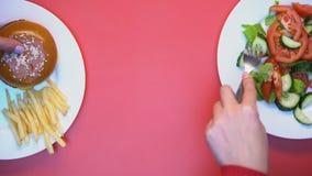 Clientes del restaurante que toman la comida de las placas blancas en el fondo rosado, almuerzo metrajes
