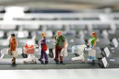 Clientes diminutos com carrinho de compras imagens de stock royalty free
