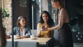 Clientes do café das meninas que fazem o pagamento em linha com o smartphone que fala à empregada de mesa