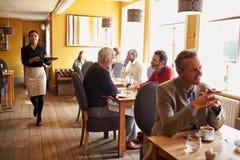 Clientes em tabelas e em empregada de mesa no interior ocupado do restaurante imagem de stock royalty free