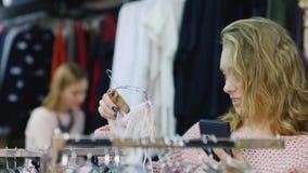 Clientes en la ropa del ` s de las mujeres de la tienda Una mujer que mira una foto en su teléfono y coge su compra, en metrajes