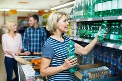 Clientes fêmeas que compram a água no hipermercado Fotos de Stock Royalty Free