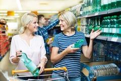 Clientes femeninos que compran el agua en hipermercado Imagen de archivo