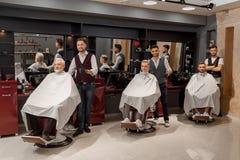 Clientes masculinos que se sientan en las sillas del peluquero cubiertas con corte de pelo fotos de archivo