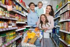 Clientes positivos con los niños que compran comida en hipermercado Imagenes de archivo