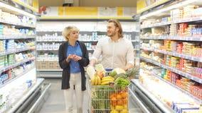 Clientes positivos da família com o trole completo de vegetais e de frutos orgânicos saudáveis na mercearia vídeos de arquivo