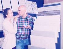 Clientes positivos dos esposos que escolhem o azulejo da cozinha Fotos de Stock Royalty Free