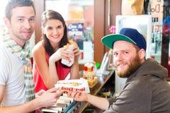 Clientes que comen el perrito caliente en snack bar de los alimentos de preparación rápida Fotos de archivo