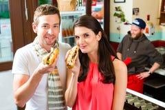 Clientes que comen el perrito caliente en snack bar de los alimentos de preparación rápida Imagen de archivo libre de regalías
