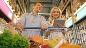 Clientes que compram no supermercado e na lista de verificação de produtos no PC da tabuleta video estoque