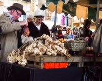 Clientes que compram o alho em um mercado Fotografia de Stock Royalty Free