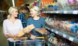 Clientes que compram o pão na loja de alimento Imagem de Stock