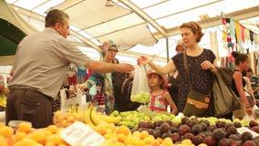 Clientes que compran ciruelos del vendedor en el bazar más grande y apretado de la ciudad Esmirna - Turquía almacen de metraje de vídeo