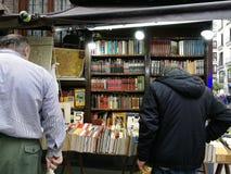 Clientes que eligen los libros usados en una librería de la calle imagenes de archivo