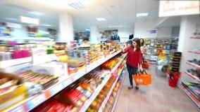 Clientes que eligen productos en supermercado almacen de metraje de vídeo