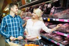Clientes que escolhem a carne Fotografia de Stock Royalty Free