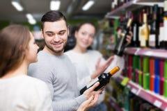 Clientes que escolhem a garrafa do vinho na loja de bebidas Fotografia de Stock