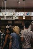 Clientes que esperam o alimento no contador no supermercado fino de Katz em novo fotos de stock