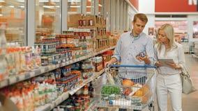 Clientes que hacen compras en supermercado y la lista de comprobación de productos en Tablet PC almacen de video