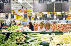 Clientes que hacen compras para las tiendas de comestibles en el supermercado foto de archivo libre de regalías