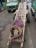 Clienti aspettanti addormentati dell'uomo indiano per trasportare il loro carico in Calcutta Fotografia Stock