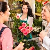 Clienti delle donne che comprano rosa del negozio di fiore della scheda Fotografia Stock