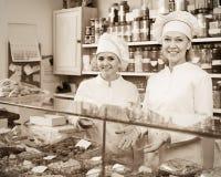 Clienti di saluto del personale femminile in confetteria Immagini Stock
