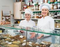 Clienti di saluto del personale femminile in confetteria Immagine Stock