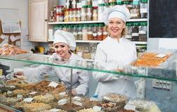 Clienti di saluto del personale femminile in confetteria Fotografia Stock Libera da Diritti