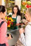 Clienti felici delle donne che comprano il mazzo del girasole dei fiori Immagini Stock
