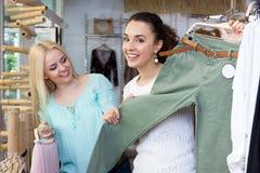Clienti femminili che scelgono nuovo indumento fotografia stock libera da diritti