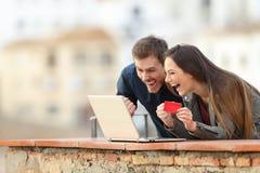 Clienti online emozionanti che trovano le offerte sulla vacanza fotografia stock